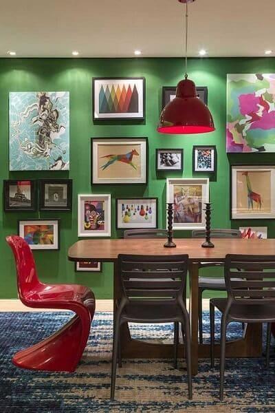 Cores complementares: parede de quadros verde e cadeira vermelha (foto: Pinterest)