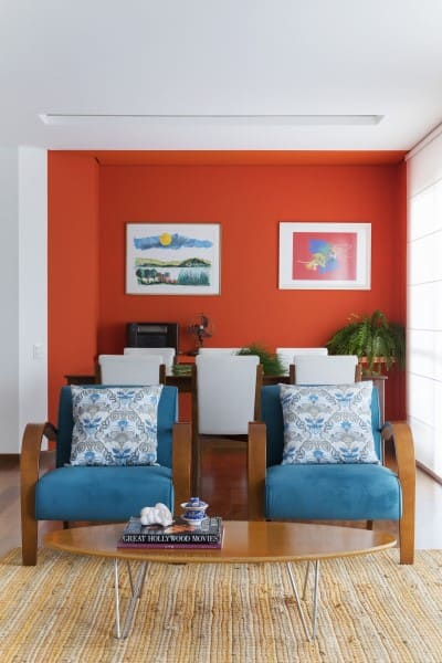 Cores complementares: parede laranja e poltrona azul (projeto: MIS Arquitetura e Interiores)