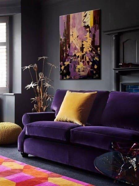 Cores complementares: sofá e quadros roxos com almofada amarela (foto: Pinterest)