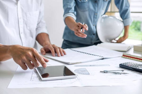 Profissionais discutindo sobre mesa com dispositivos móveis e planta de projeto