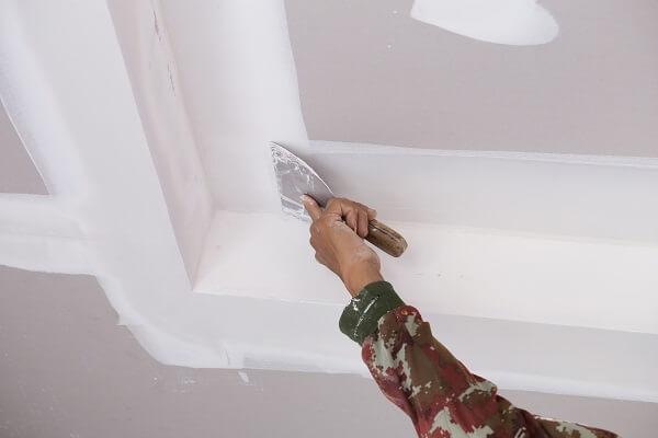 Profissional da construção civil aplicando gesso