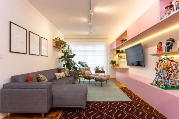 Sofá com estofado cinza e rack planejado rosa (projeto: Motirõ Arquitetos)