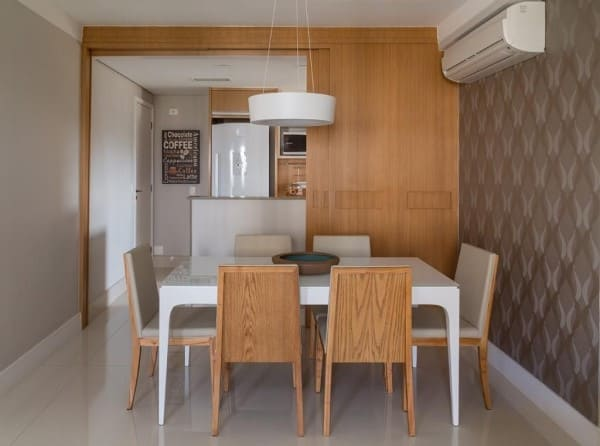 Madeira clara na parede e nas cadeiras cria decoração harmônica (projeto: Ana Yoshida)