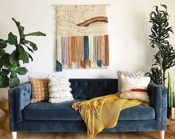 Tapeçaria colorida atrás de sofá azul (projeto: Pinterest)