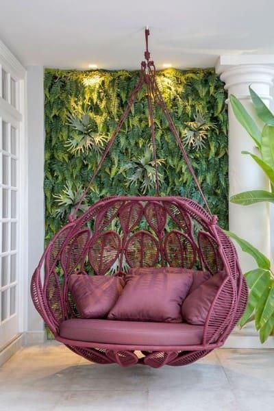 Muro verde e cadeira de balanço fixada no telhado com corda náutica (foto: Revista Viva Decora)