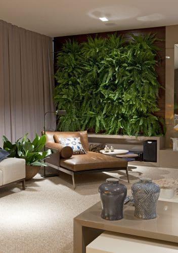 Muro verde em sala de estar com cadeira de couro e luminária de piso cinza (foto: Revista Viva Decora)