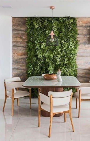 Muro verde em varanda com mesa de madeira (foto: Revista Viva Decora)