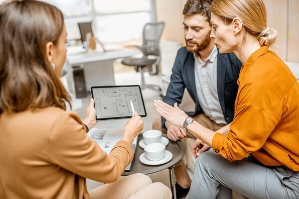 Profissional debatendo planta de projeto com clientes