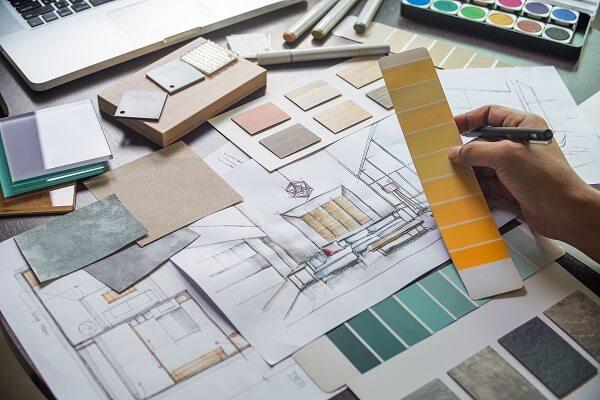 Profissional observando desenho e amostras de cores e revestimentos
