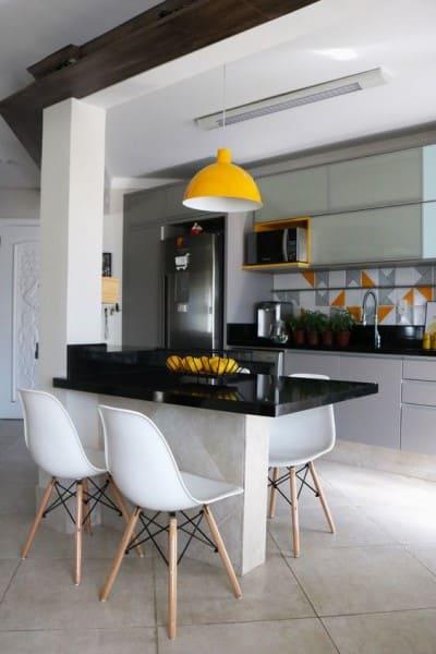 Balcão de alvenaria para cozinha americana com tampo de granito e cadeira eames (foto: Pinterest)