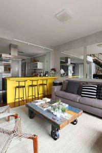 Ambiente integrado mescla tons de cinza e amarelo