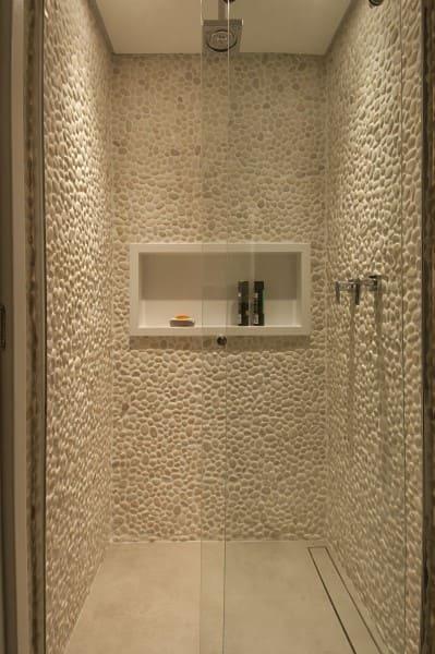 Nicho de porcelanato branco em box revestido com pedra clara (projeto: Bruno Moraes Arquitetura e Interiores)