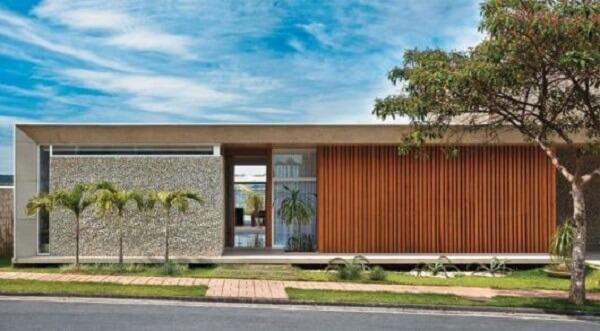 Concreto aparente com acabamento ripado em madeira valoriza a fachada do imóvel