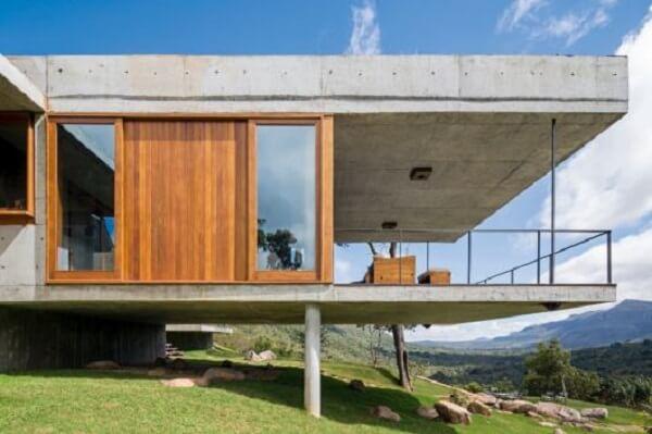Concreto aparente e ripas de madeira estruturam a fachada da casa