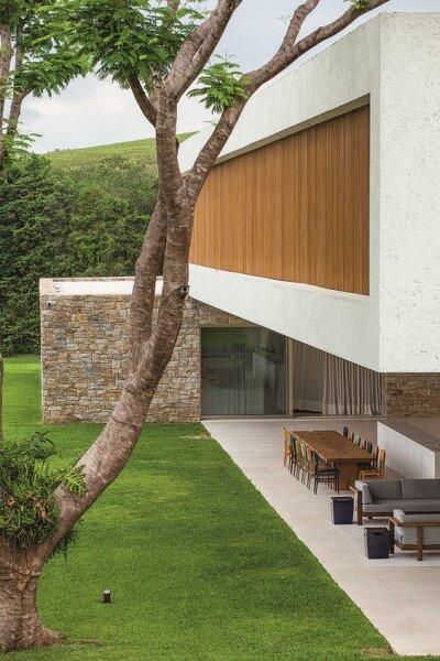 Casa suspensa com painel de madeira e viga em balanço (projeto: Luiz Fernando Rocco)