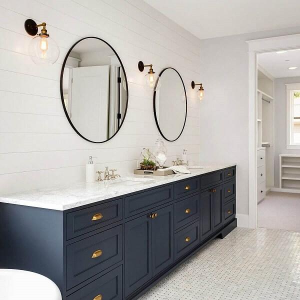 Decoração clássica com gabinete planejado azul e luminária de banheiro parede