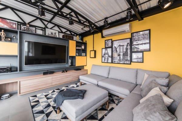 Estilos de casas: sala de estar contemporânea com parede amarela e sofá cinza (projeto: Pietro Terlizzi)