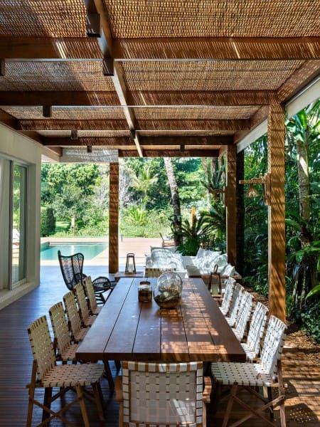 Estilos de casas: casa de praia com mesa de madeira e sofá estofado branco (projeto: Patricia Bergantin Arquitetura e Interiores)