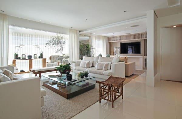 Estilos de casas modernas: sala de estar com tons neutros e mesa de centro de vidro (projeto: Andrea Teixeira e Fernanda Negrelli)