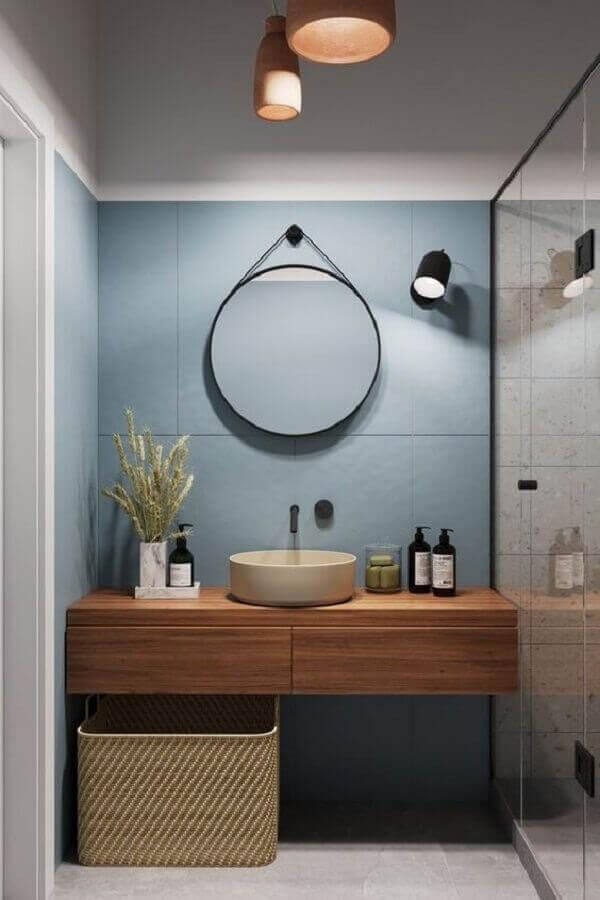 Luminária de banheiro de parede e bancada de madeira decoram o espaço