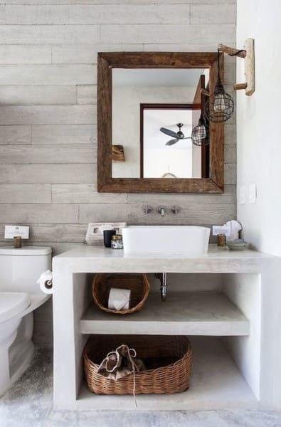 Móveis de alvenaria: bancada de banheiro com concreto aparente e espelho com moldura de madeira (foto: Pinterest)