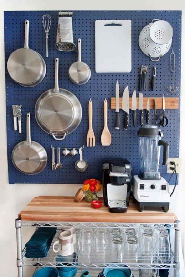 O pegboard azul decora e organiza itens da cozinha
