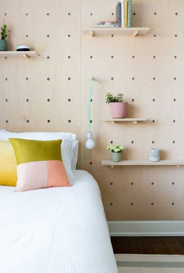 O pegboard madeira preenche toda a parede do dormitório e sustenta prateleiras