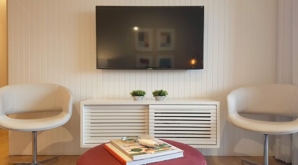 Lambris: parede de lambri branca faz suporte para a TV (projeto: Tatiana Baroni)