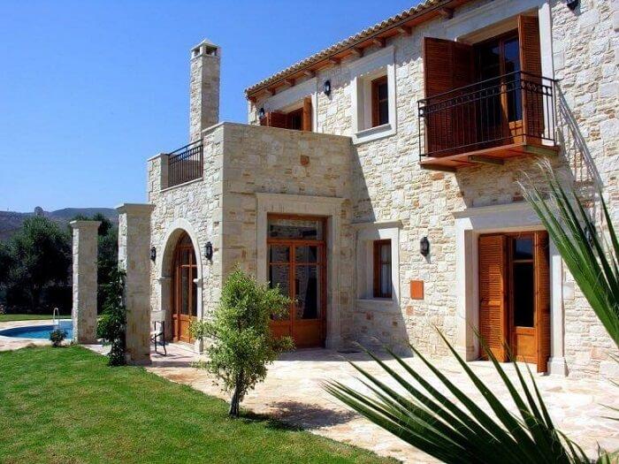 Casa colonial moderna com fachada revestida em pedra e elementos em madeira. Fonte: Pinterest