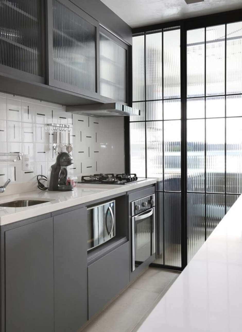 A porta dos armários e porta de correr que divide a lavanderia da cozinha é feita de vidro fantasia canelado. Fonte: Pinterest