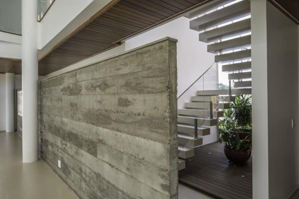 Escada em U de concreto com guarda-corpo de vidro (foto: Barillari Arquitetura)