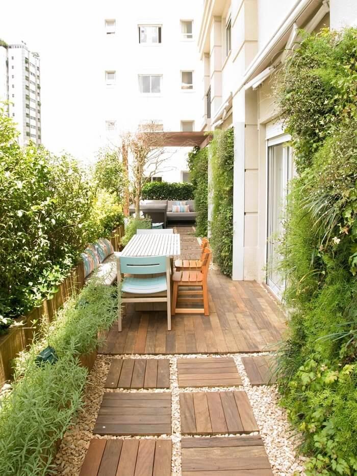 Área social do condomínio com pisante de madeira para jardim. Projeto de Gigi Botelho Paisagismo