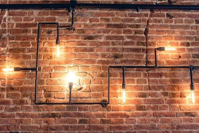 Iluminação industrial: as lâmpadas de filamento em tubulações trazem personalidade ao projeto. Fonte: Viviana Reis