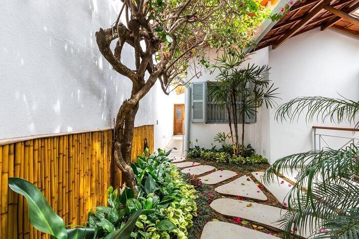 Parede com bambu natural, vegetação diversificada e pisante para jardim com pedra. Projeto de BY Arq&Design