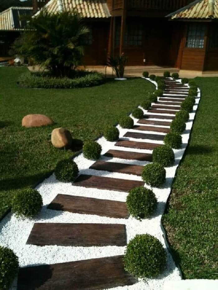 Pisante de madeira para jardim com acabamento em pedras brancas. Fonte: Pinterest