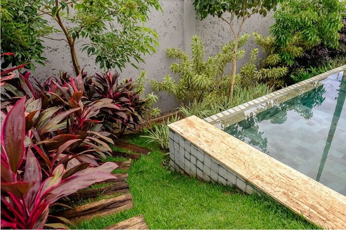 Piscina com revestimento azul, vegetação natural e pisante para jardim de madeira. Projeto de Andréa Esteves