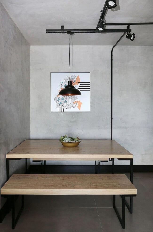 Projeto com parede de cimento queimado, mesa de madeira e iluminação industrial. Fonte: Casa de Valentina