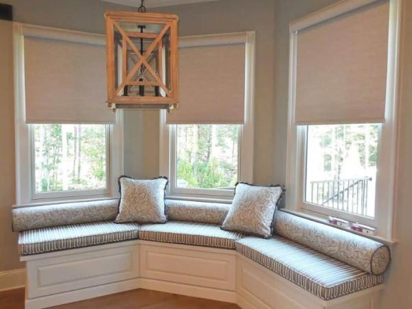 Bay Window sofá branco e pendente de madeira criam composição aconchegante (foto: @ladydianneswindowtreatments)
