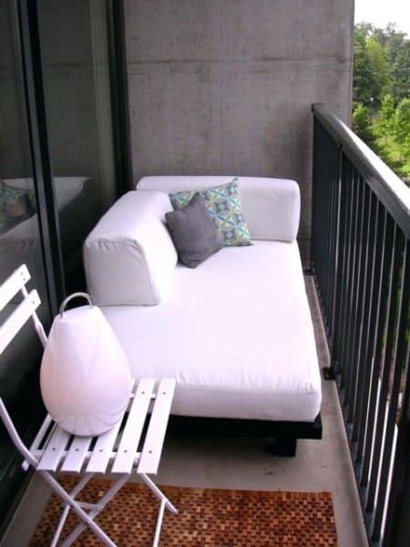 Chaise longue branca com almofadas em varanda (foto: Casa e Construção)