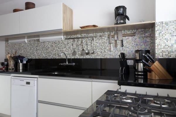 Granito Preto São Gabriel em bancada de cozinha com parede de pastilhas coloridas (foto: Adell e Porto)