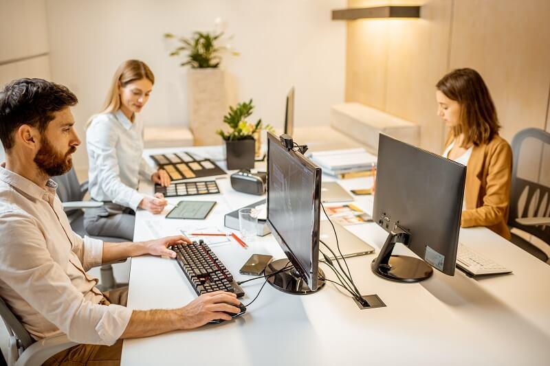 Software de gestão: arquitetos trabalhando juntos sobre mesa no escritório.