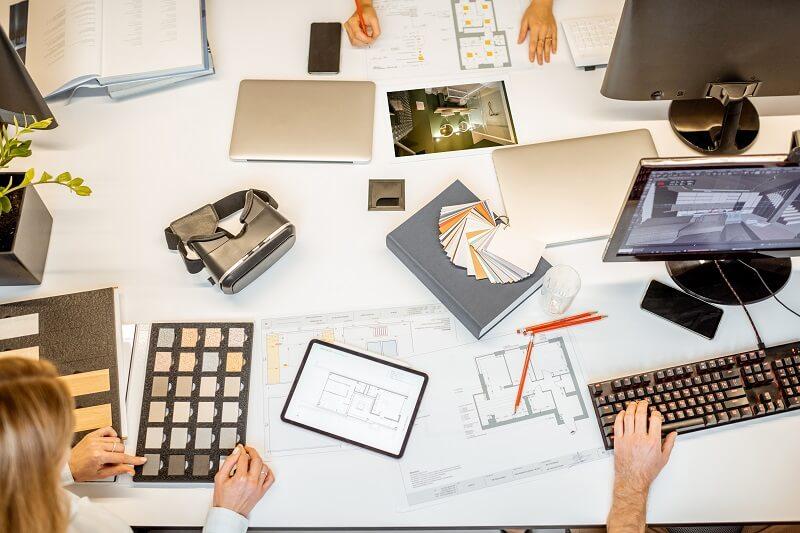 Software de gestão: materiais e plantas utilizados no desenvolvimento de projeto sobre mesa do escritório.