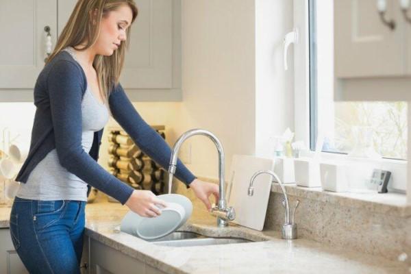 Torneira para cozinha: pessoa lavando a louça (foto: VIX)