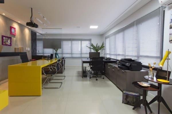 Cortina para escritório: persiana de alumínio clara e bancada amarela (foto: Natalia Pini)
