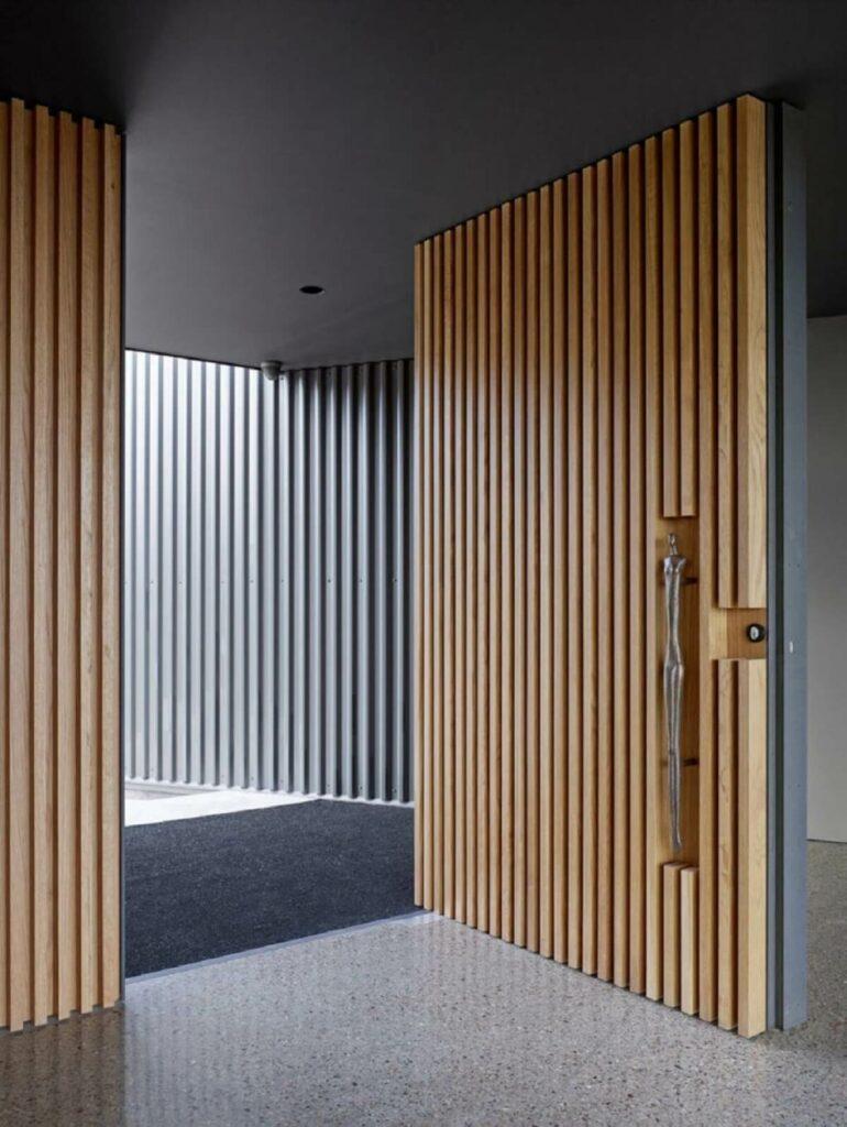Hall de entrada com porta ripada. Fonte: ConstruindoDecor