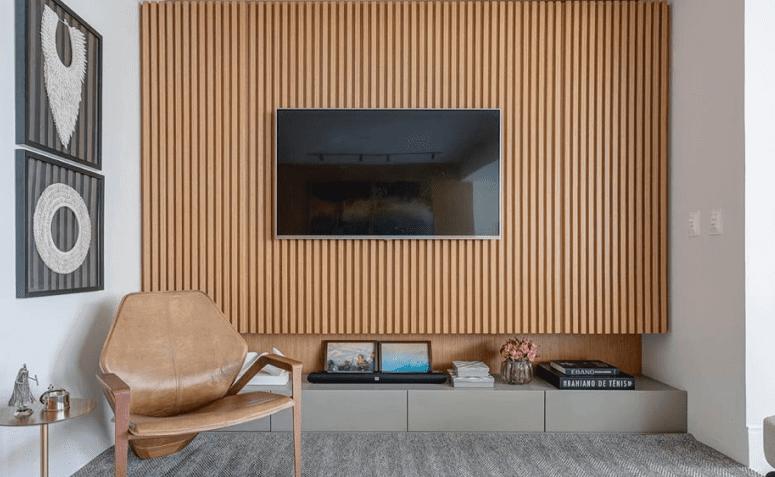 Materiais naturais: painel ripado de madeira decora a sala de TV. Fonte: Pires e Medeiros Arquitetura