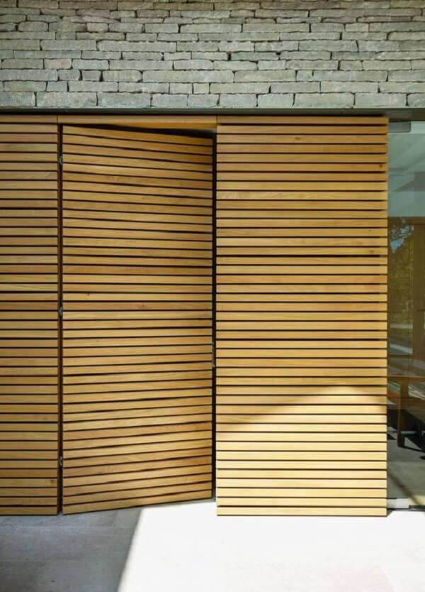 Parede de pedra e porta ripada de madeira. Fonte: ArchDaily